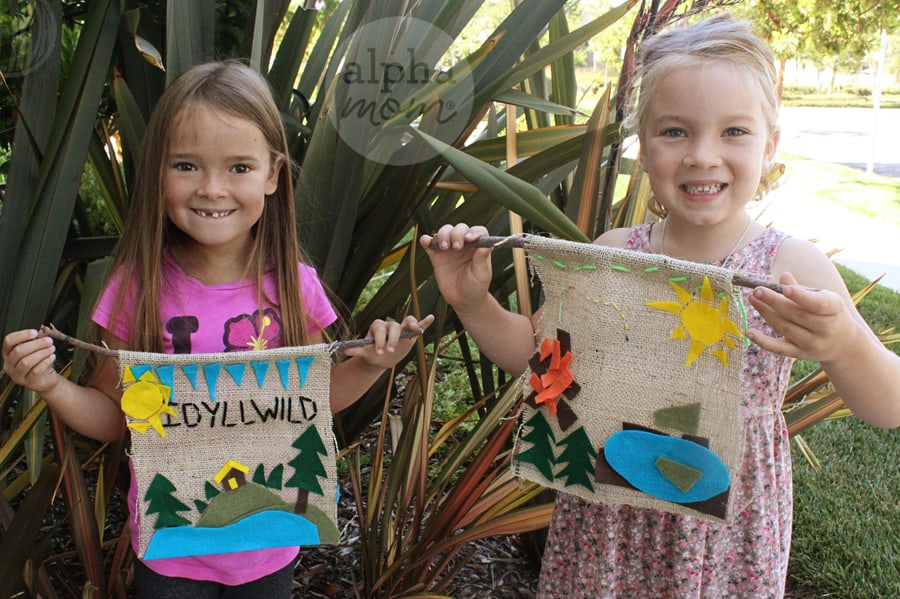 two yung girls holding up their handmade Camp banners