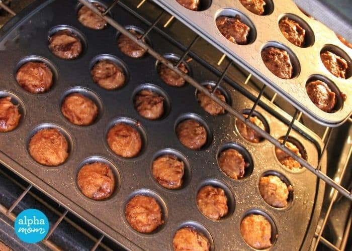 two mini muffin pans of dozens of Whole Wheat Chocolate Swirl Muffins with Butternut Squash and Apples baking in the oven