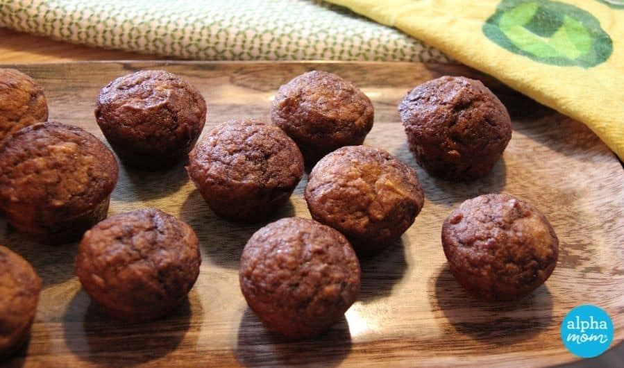 closeup of Whole Wheat Chocolate Swirl Mini Muffins with Butternut Squash and Apples lined up on a wooden tray with decorative yellow napkin in background