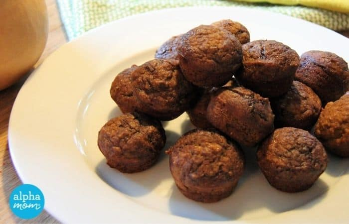 close-up photo of many Whole Wheat Chocolate Swirl Mini Muffins with Butternut Squash & Apples stacked high on a white dinner plate
