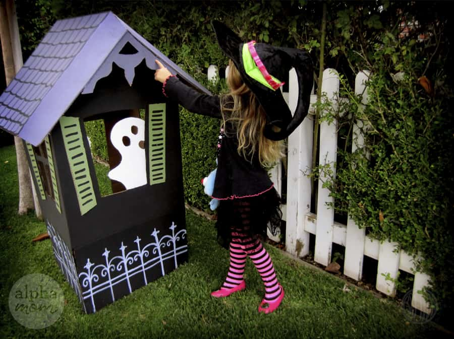 little blond girl in witch's costume with hat and pink and black striped stockings wither back turned and pointing toward handmade black cardboard house with white roof and ghost peeking through the window