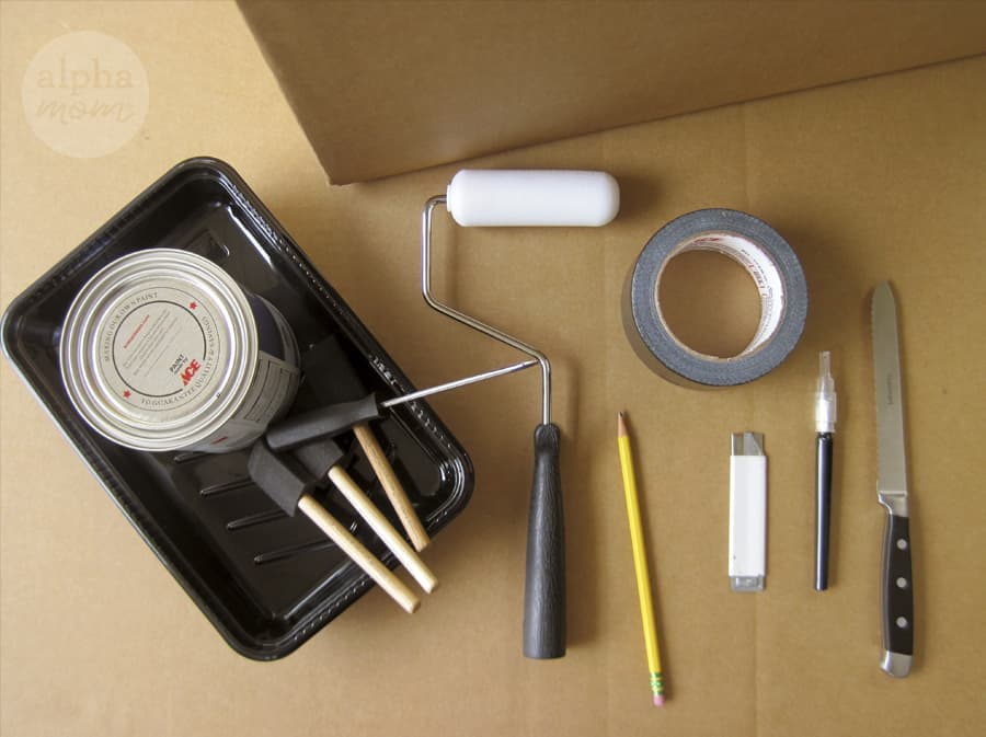 overhead photo of supplies to make Halloween life-size haunted house including paint roller, x-acto knife and duct tape.