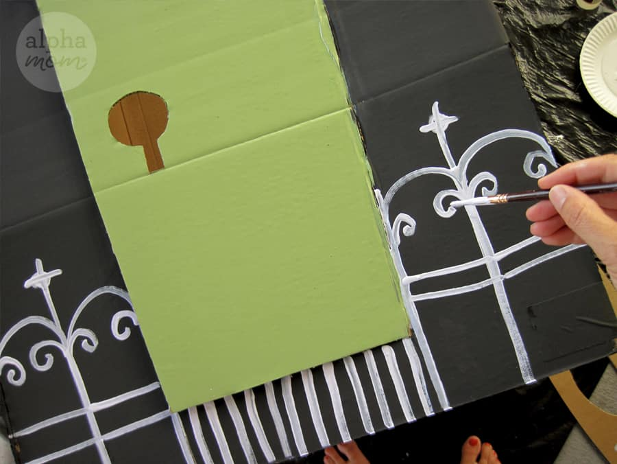 close-up of hand painting white fence detail onto black cardboard haunted house with green door for Halloween