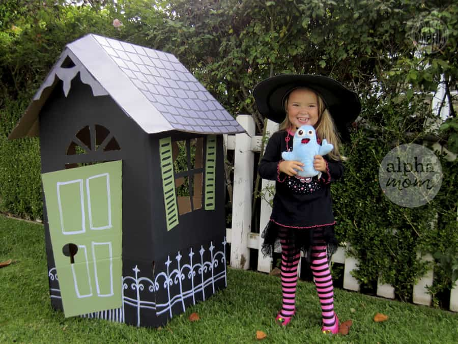 little blond girl in witch's costume and hat outdoors next to a handmade life-sized cardboard haunted house with white roof and green door and shutters