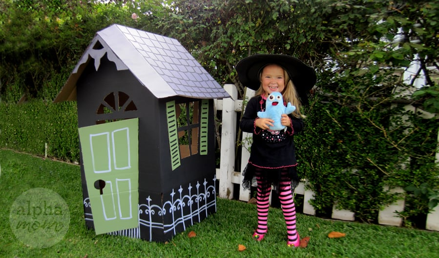Smiling little girl dressed in witch costume holding a ghost stuffie next to a black life-sized haunted house made from cardboard boxes with white roof and green door