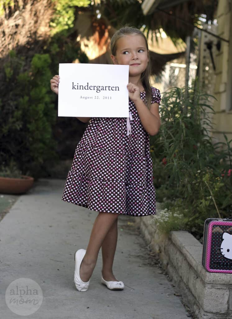 """Young girl wearing a polka dot dress and looking to the side while posing for a photo while holding a sign that says """"kindergarten"""""""