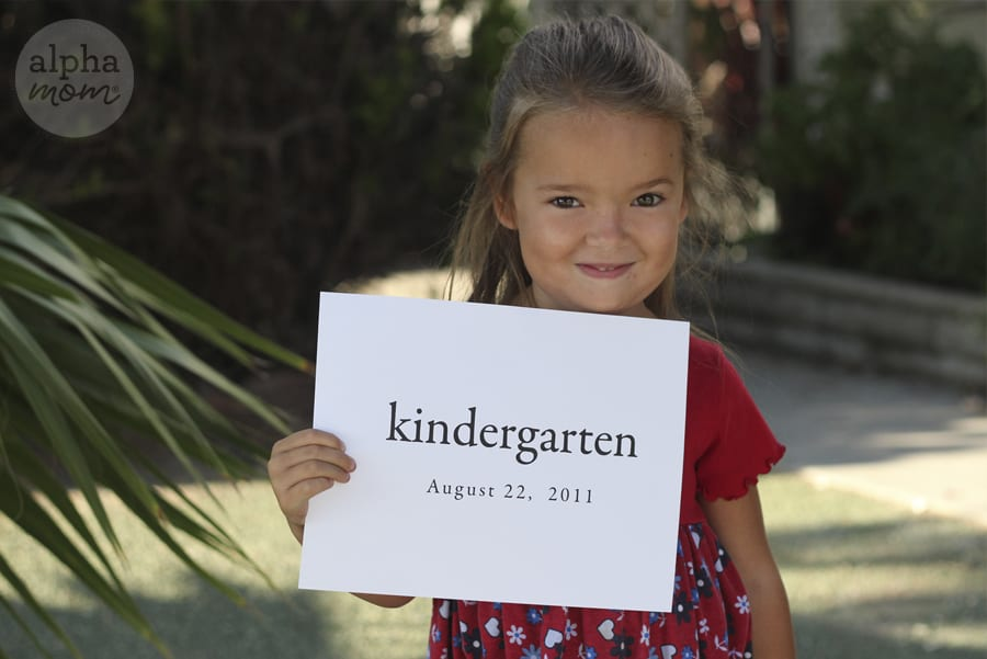 smiling blond girl holding up a piece of paper that says kindergarten