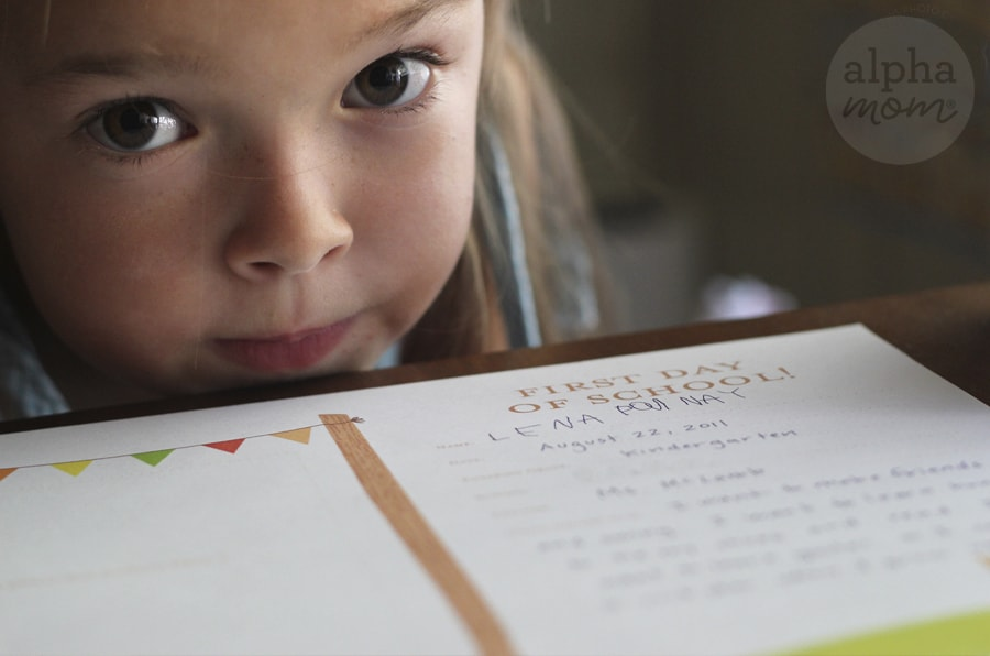 child at a table looking into the camera with First Day of School Printable in front of her