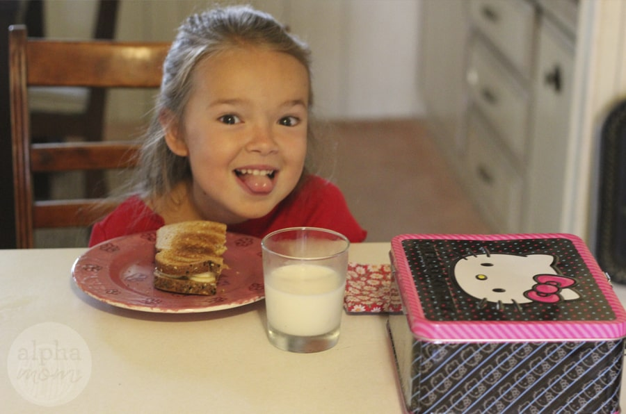 smiling child enjoying breakfast at the kitchen table and sticking her tongue out at camera with Hello Kitty lunch box at foreground