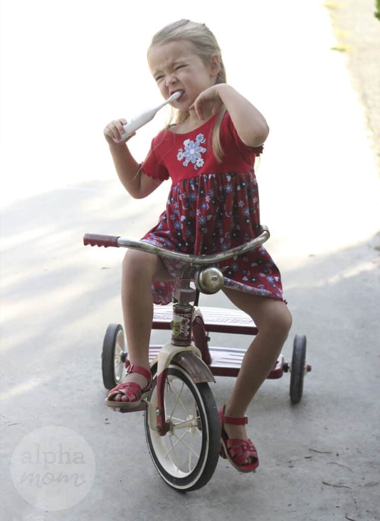 young girl brushing her teeth while riding a red tricycle