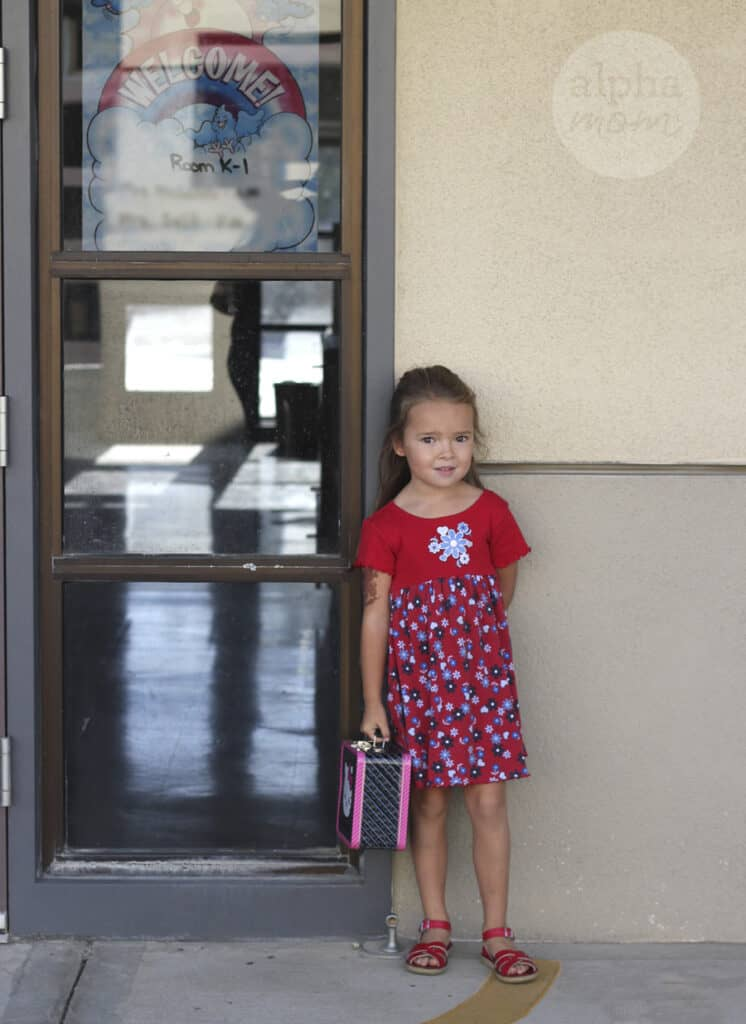 young girl in a red dress and sandals carrying a Hello Kitty metal lunch box standing by her classroom door