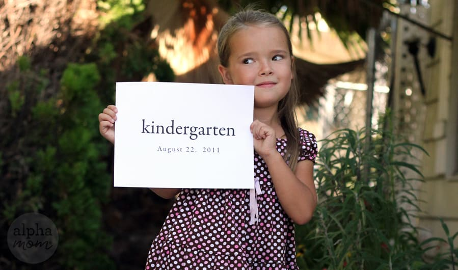 """Young girl wearing a dress posing for a photo while holding a sign that says """"kindergarten"""""""