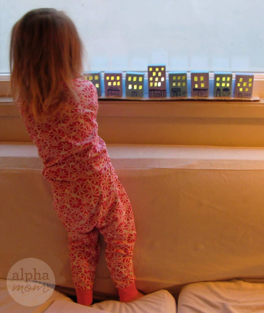 photo of little girl from behind standing on a sofa and facing her craft which is row of tiny cardboard houses lit up in yellow on the windowsill