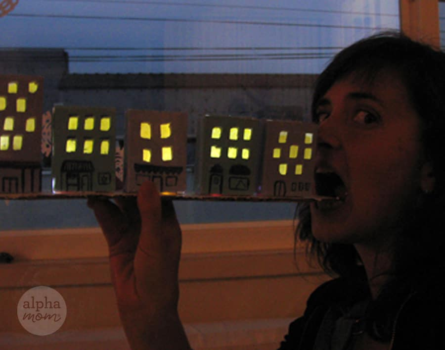 funny photo of Brenda Ponnay with her mouth open making believe she is eating the tiny row of cardboard houses like they are a long subway sandwich