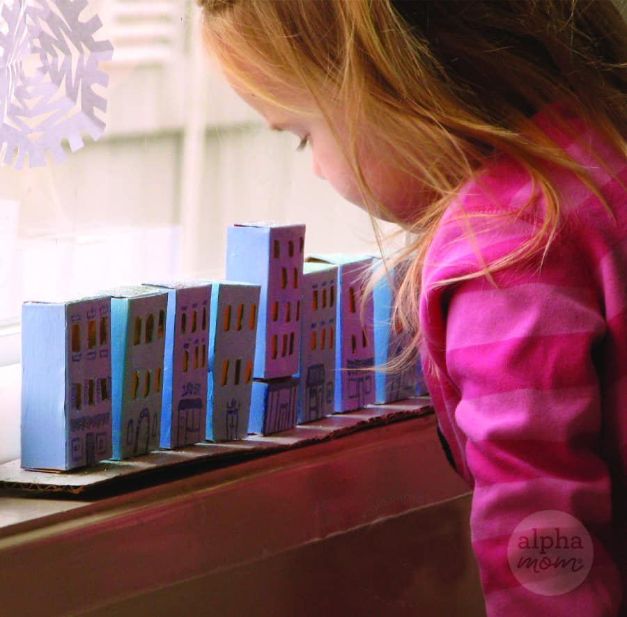 little blond girl in pink shirt looking down on craft row of small cardboard houses lined up on window sill and mimicking village