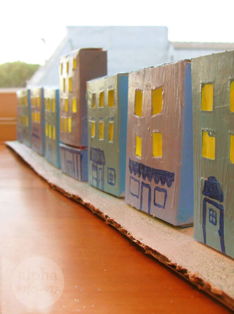 close-up photo of Little Hanukkah Village craft made of cardboard and painted light blue with glitter