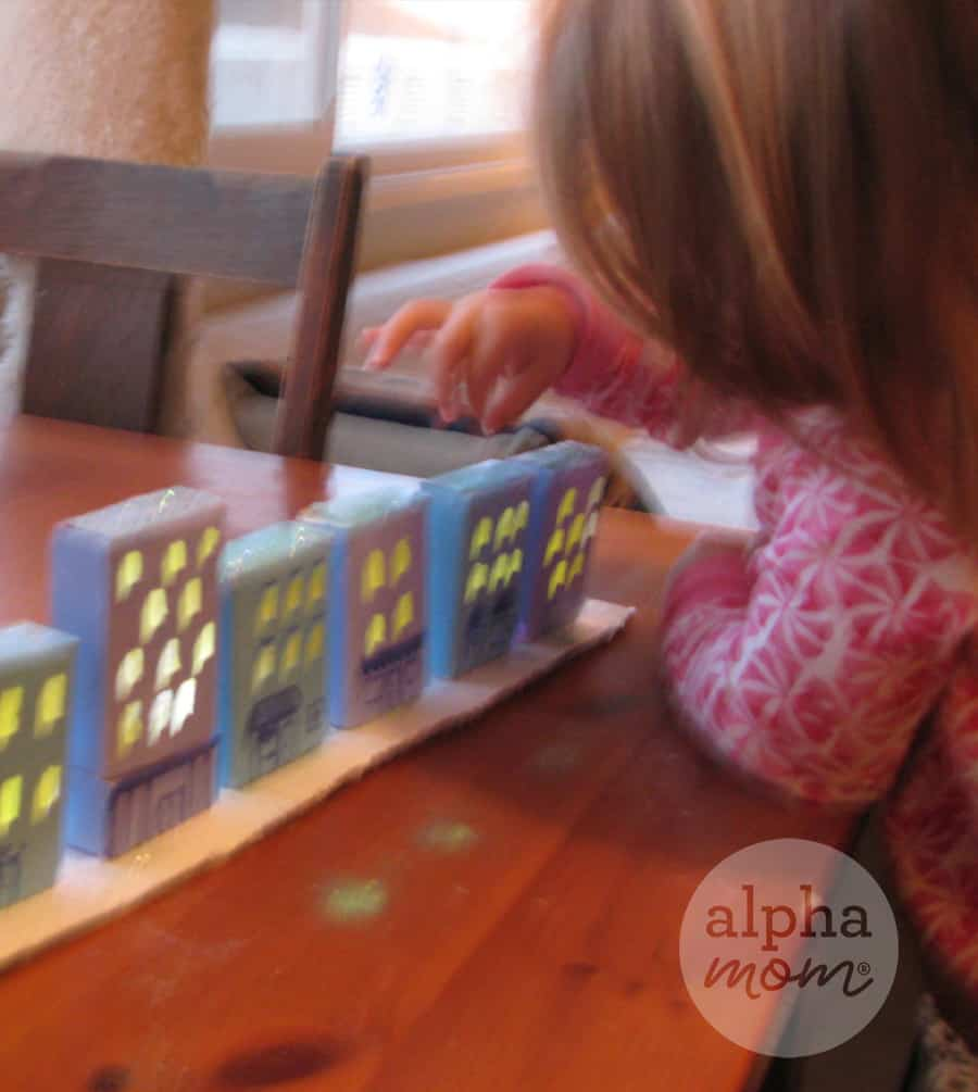 blurry photo of little girl adding glitter snow to the rooftops of craft of paper village composed of homes