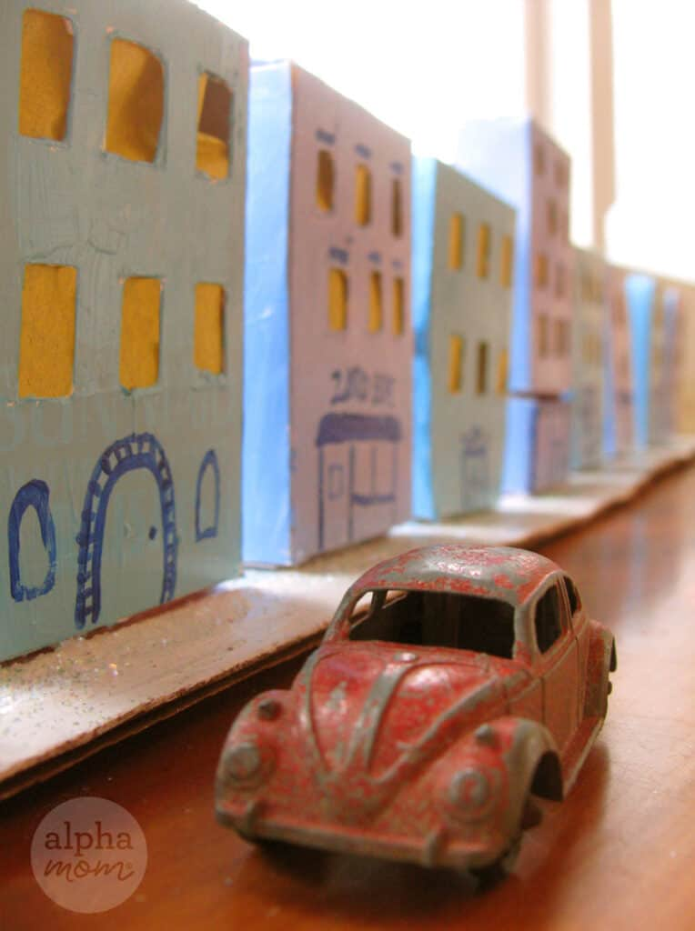 close-up of vintage and worn red toy VW buggy toy car in front of tiny cardboard blue houses in village craft for Hanukkah