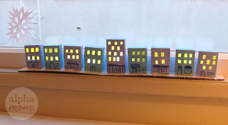 craft of nine tiny blue cardboard houses lined up next to each other made to look like a little village with their windows lit up and glowing yellow