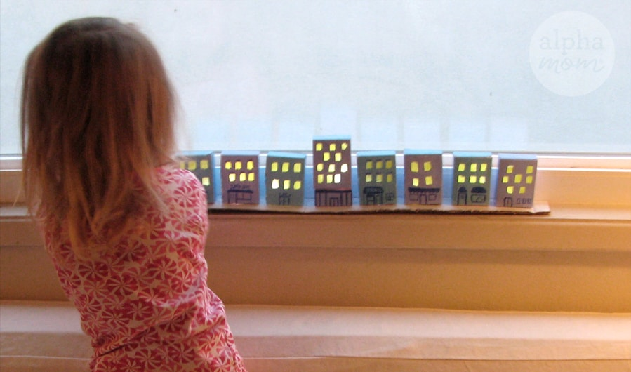 photo of little girl from behind facing her craft of little cardboard houses lined up and painted blue with yellow windows made to look like a village