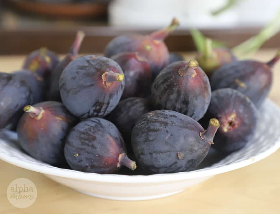 close-up photo of a white bowl filled with about 20 fresh ripe figs