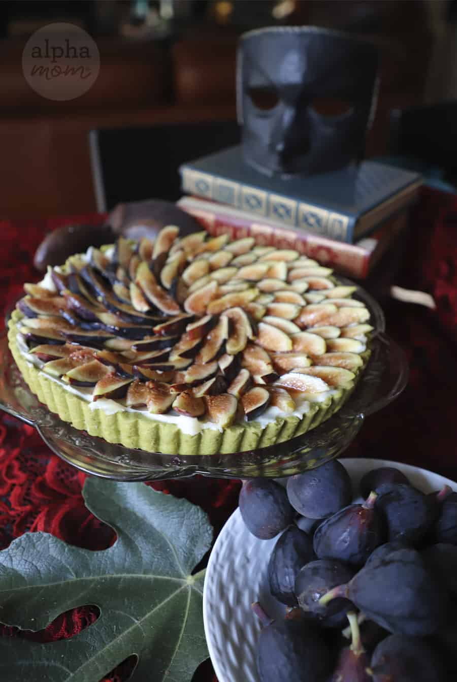 photo of fresh sliced fig tart with green match crust on glass cake stand with bowl of fresh fig in foreground and stack of books and decorative mask in background
