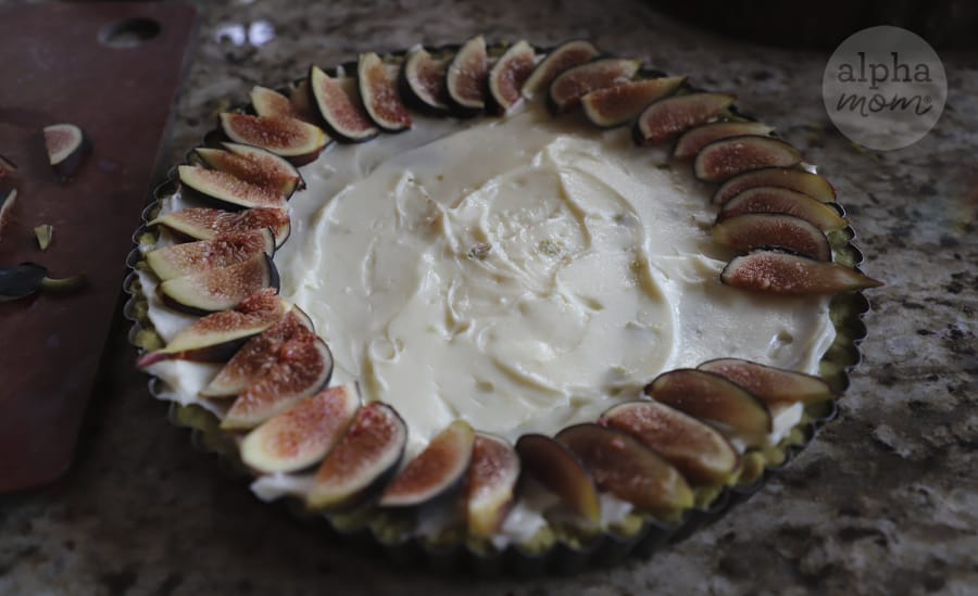 overhead photo of making of sliced figs being positioned around cream cheese filling on tart