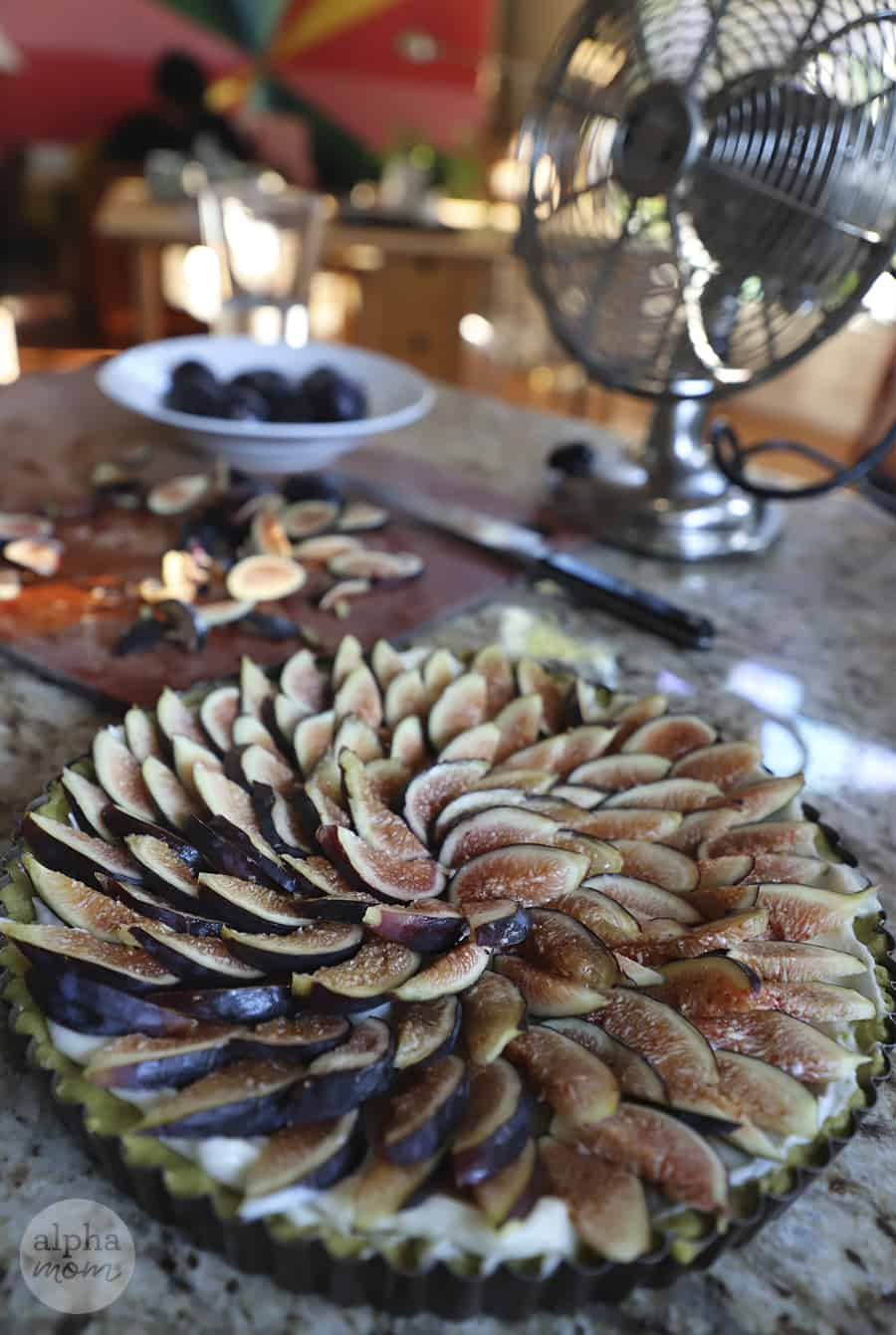photo of completed freshly sliced fig tart in front with scraps on cutting board in the background and fan on countertop to the right side