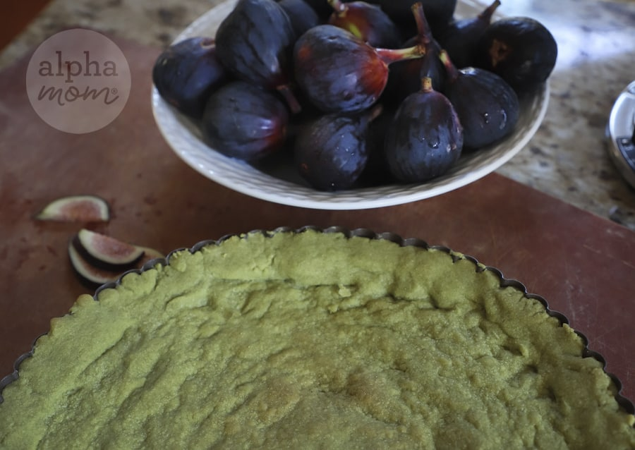 close-up of bowl of fresh figs in background and half image of baked green matcha crust in foreground