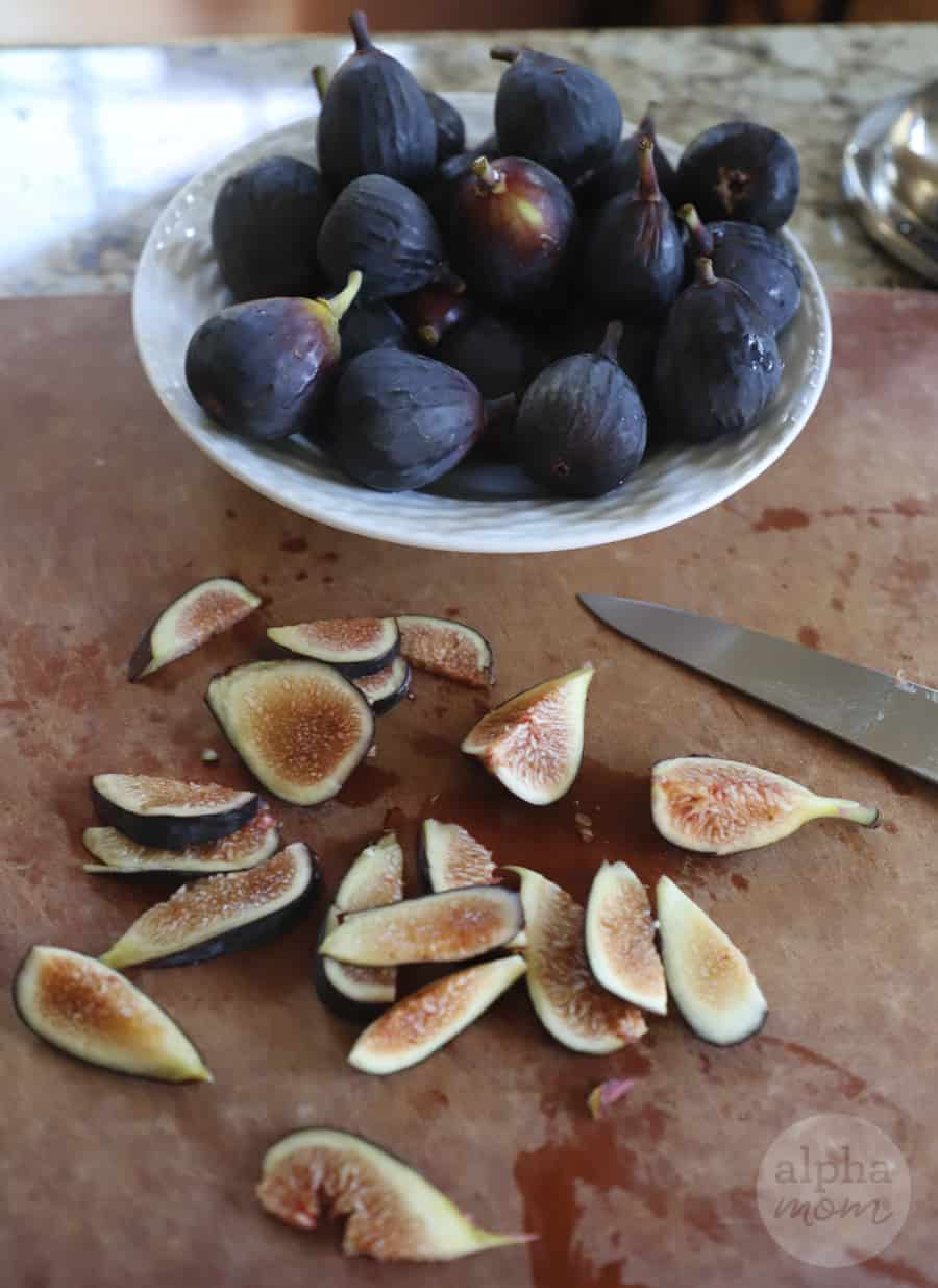overhead photo of sliced fresh figs and knife on cutting board in foreground with full bowl of whole figs in background