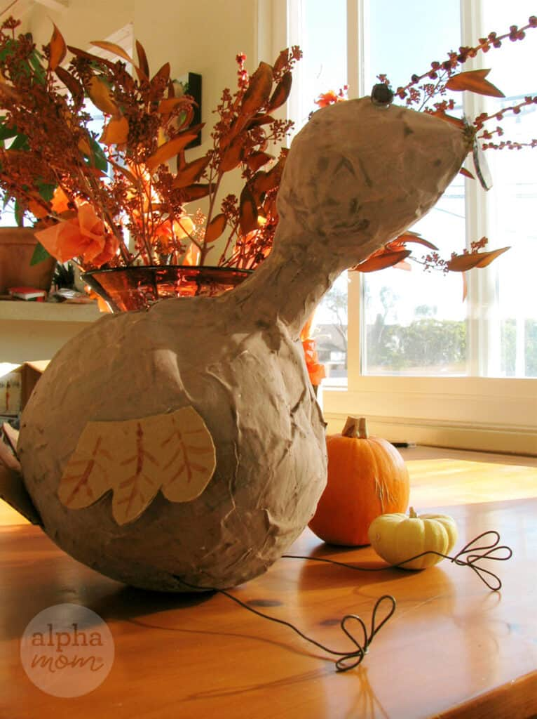 photo of large paper mache pinata made to look like a turkey with wire limbs on a table with autumn decor surrounding it