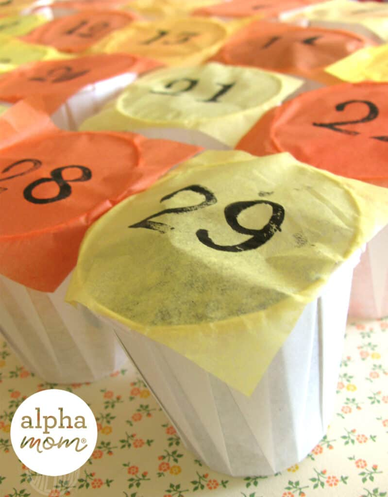 close overhead photo of alternating small dixie cups with alternating yellow or orange tissue squares printed with black numbers on them