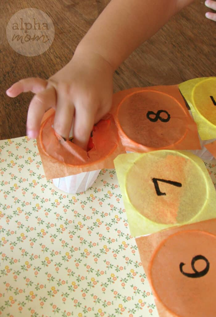 little girl's finger poking a hole through an orange tissue paper covering a dixie cup filled with leftover Halloween candy. More cups covered in alternating yellow and orange tissue with black printed numbers from 6 thru 8.
