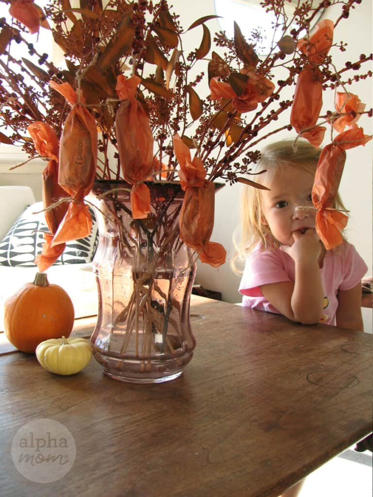 little blond toddler sucking her thumbs and sitting by a vase filled with branches from which many orange tissue papers wrapped with candy are hung