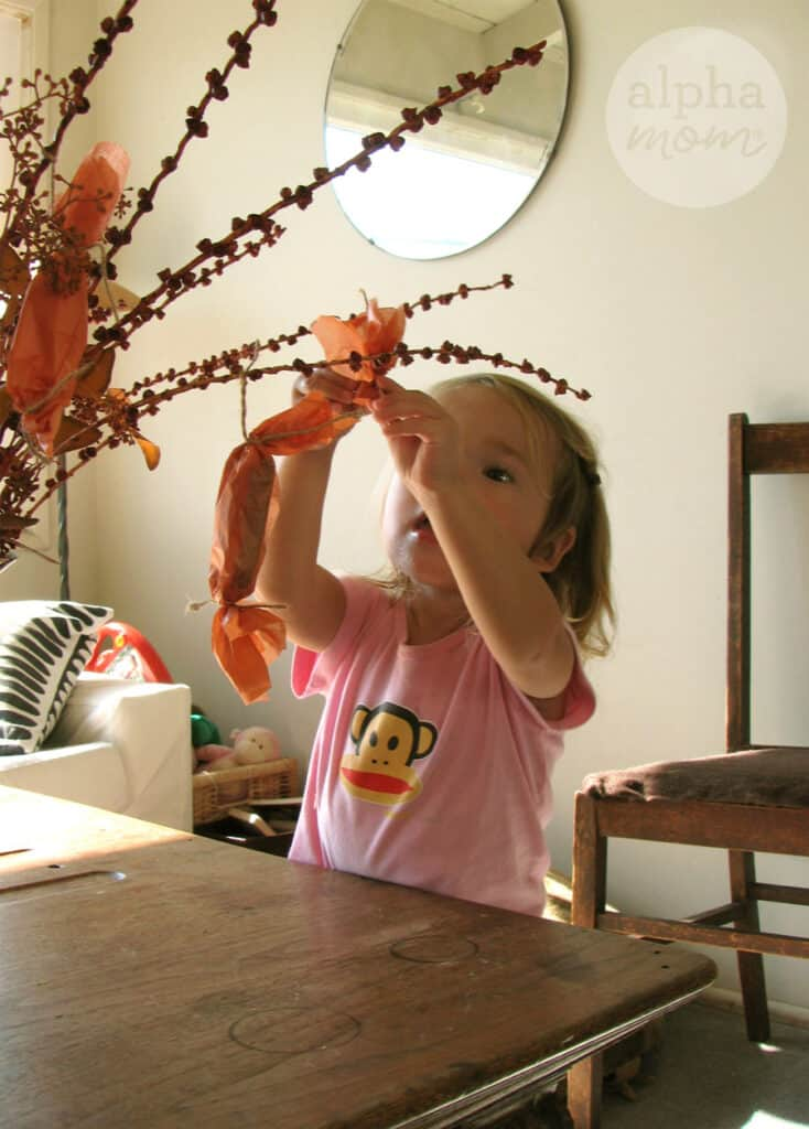 little blond girl wearing a pink t-shirt with monkey face on it hanging orange tissue wrapped with candy inside onto a branch