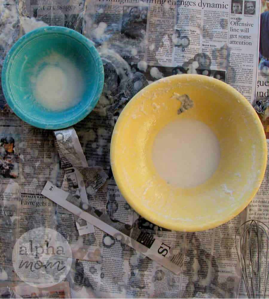 overhead photo of small yellow and turquoise bowls filled with paper mache glue ontop of table covered in newspaper
