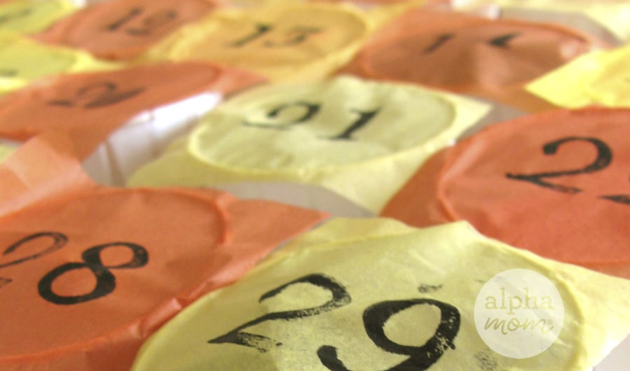 close-up of alternating orange and yellow tissue paper squares with sequential calendar numbers stamped on them with black ink covering white dixie cups
